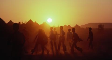 Des jeunes enfants africains faisant une partie de football au couché du soleil.